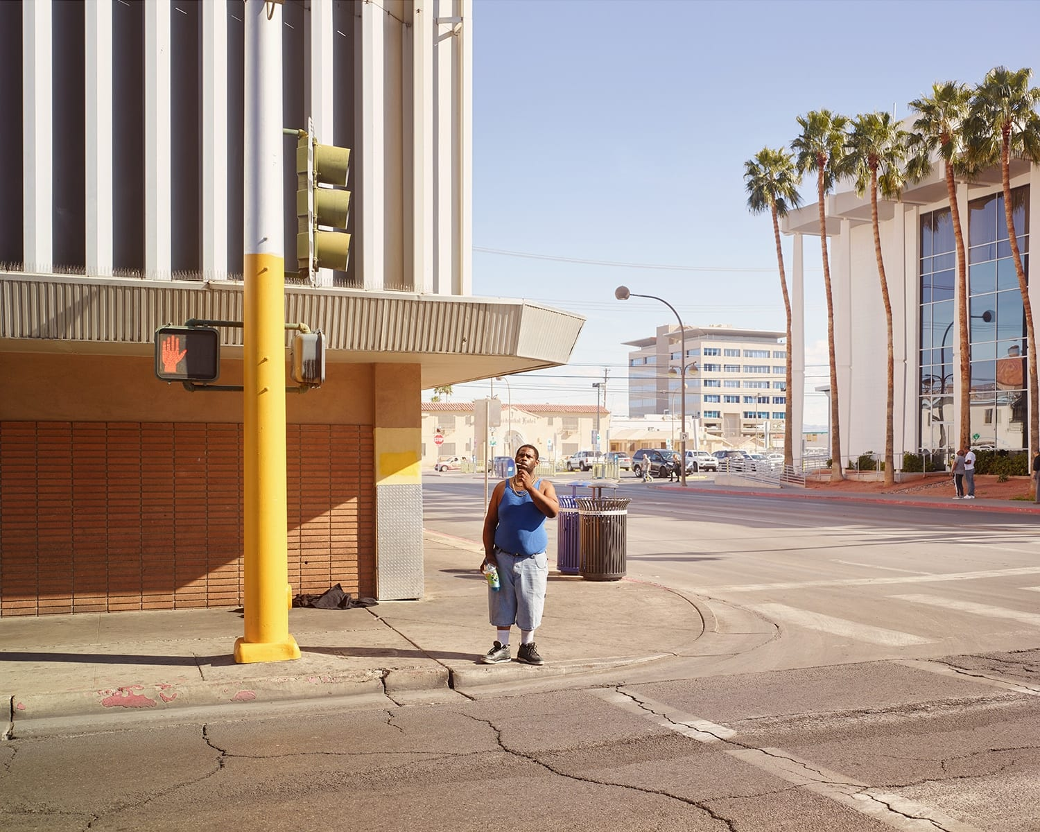 Oli Kellett Carson Ave, Las Vegas - HackelBury Fine Art London - photograph of man in blue shirt at cross walk with palm trees in background