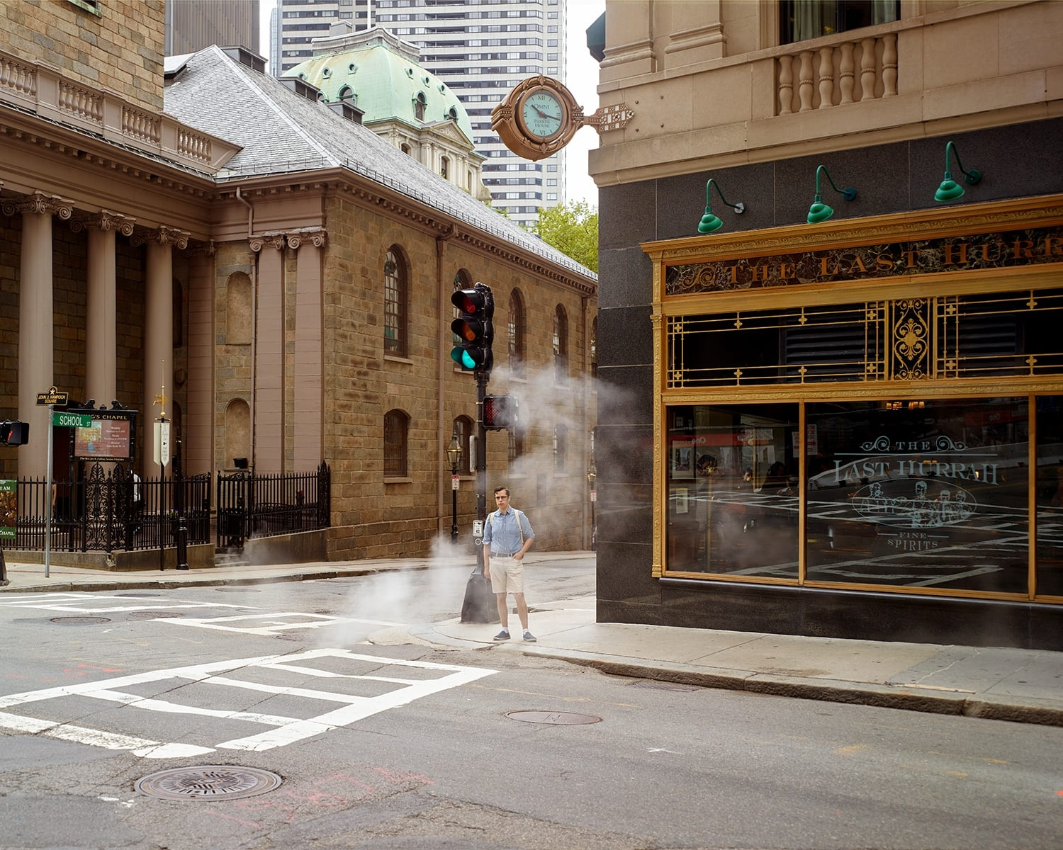 Oli Kellett Tremont St, Boston - HackelBury Fine Art London - photograph of man in blue shirt and shorts waiting at corner behind smoke