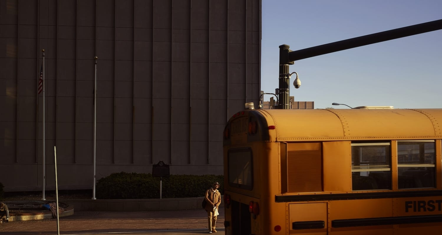 Oli Kellett PeachTree St Atlanta - HackelBury Fine Art London - photograph of yellow school bus and man waiting behind to cross street