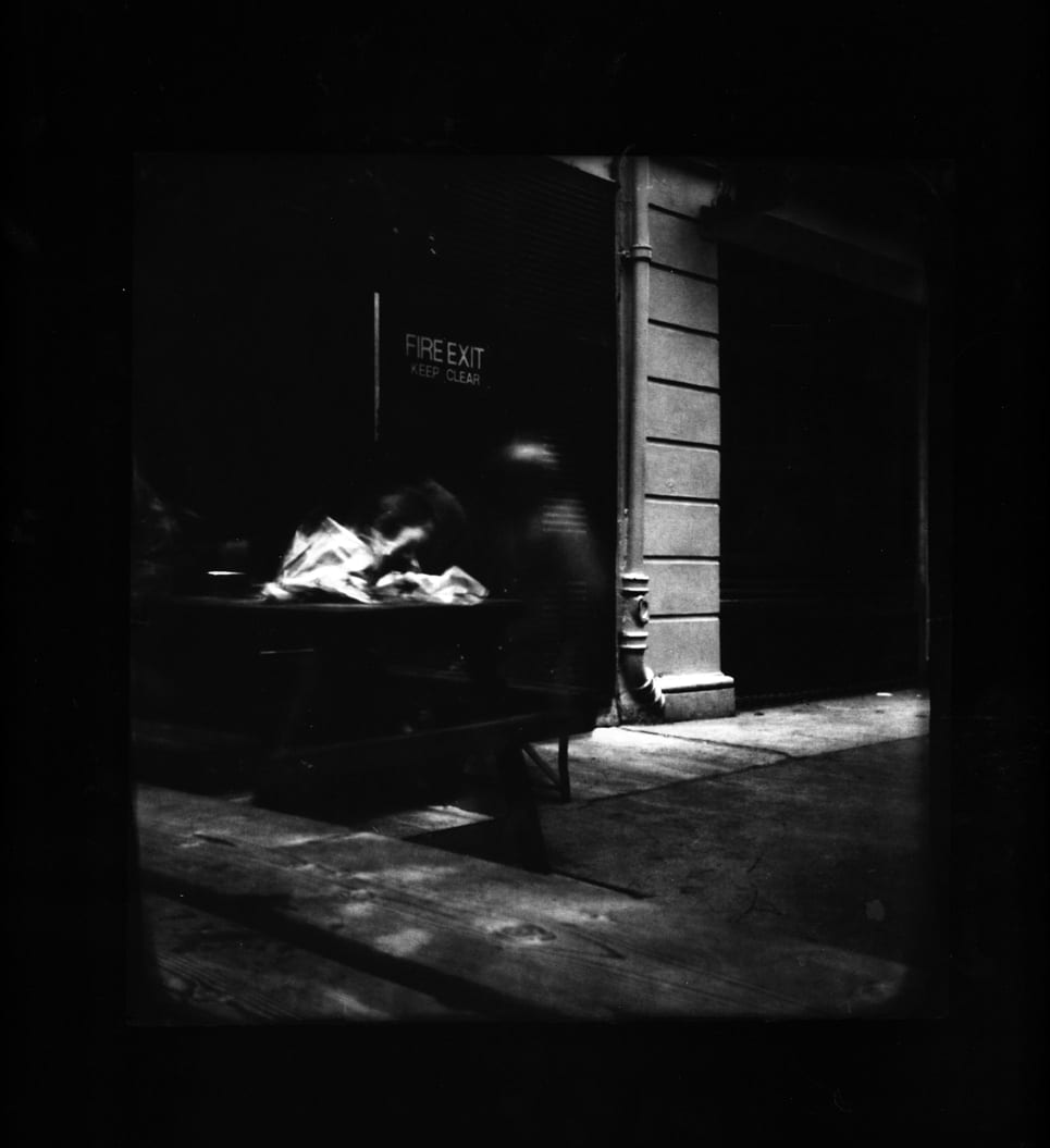 Pinhole-London 5 (off Oxford Street)-Katja Liebmann-HackelBury Fine Art-black and white photograph of blurry man at picnic table and fire exit sign
